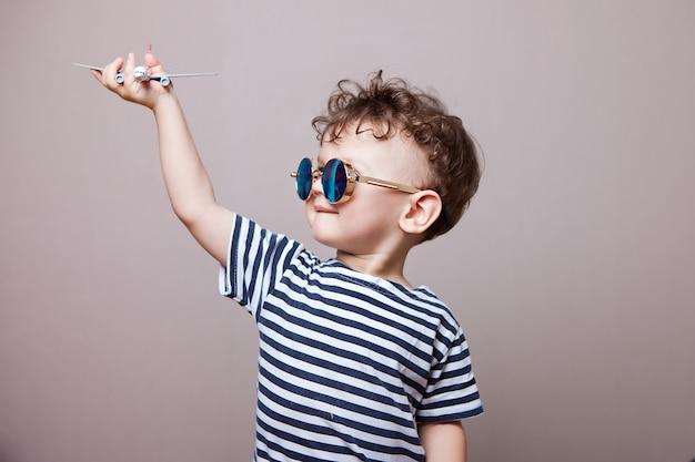 Ein junge in einem gestreiften t-shirt und einer sonnenbrille mit einem modellflugzeug spielt in seinen händen.