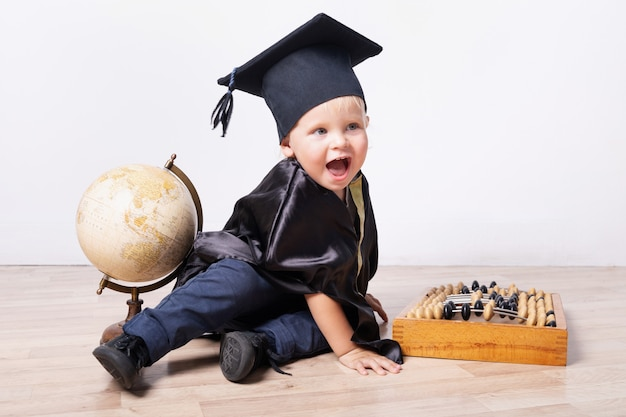 Ein junge in einem junggesellen- oder meisterkostüm mit einem globus und einem abakus. frühe entwicklung, bildung, wissenschaft, frühes lernbabykonzept
