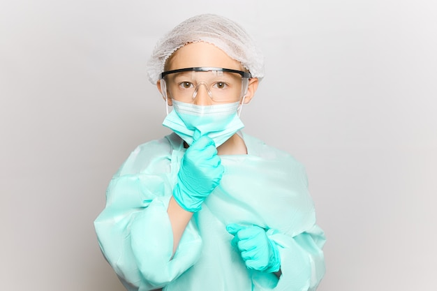 Ein junge in einem medizinischen kittel und einer maske passt die maske mit seiner hand an, die einweghandschuhe trägt