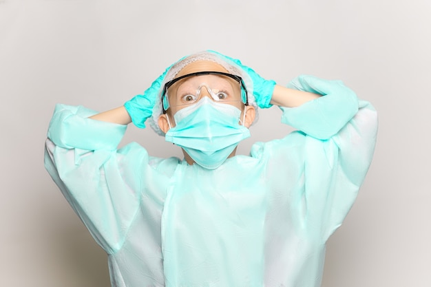 Ein junge in einem medizinischen kittel und einer maske umklammert seinen kopf mit beiden händen und schaut in die kamera