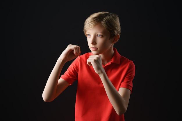 Ein junge in einem roten t-shirt mit einem kurzen haarschnitt auf schwarzem hintergrund hält seine hände wie beim boxen, einer schutzhaltung