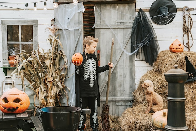 Ein junge in einem skelettkostüm mit einem hund auf der veranda eines hauses, das geschmückt ist, um eine halloween-party zu feiern