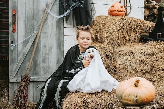 Ein junge in einem skelettkostüm mit einem hund in einem geisterkostüm auf der veranda eines hauses, das dekoriert wurde, um eine halloween-party zu feiern
