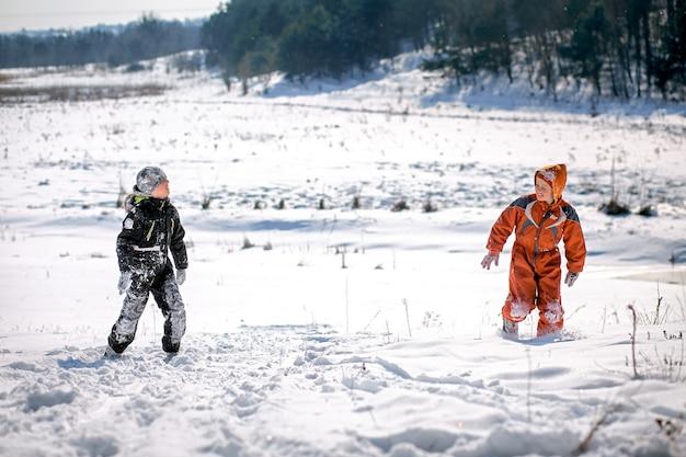 Ein junge in einem skianzug auf einem schneeberg mit einem schlitten. das kind fährt einen schlittenroller. aktive spiele auf der straße. gesunder lebensstil
