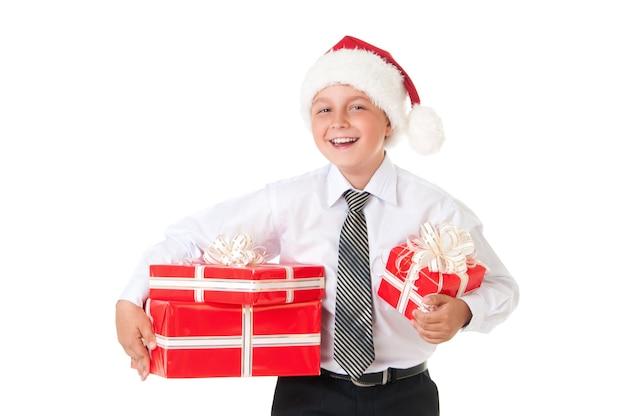 Ein junge in einem weißen hemd und einem hut von silvester weihnachtsmann mit roten geschenken isoliert