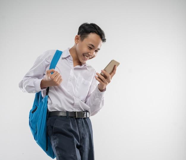 Ein junge in einer junior-high-school-uniform, der mit einer aufgeregten geste mit einem hintern auf ein handy schaut.