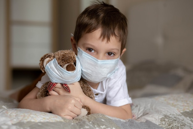 Ein junge in einer maske, der auf dem bett liegt und einen teddybären in einer maske umarmt. bild mit selektivem fokus. foto in hoher qualität