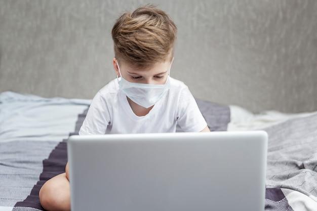 Ein junge in einer medizinischen maske sitzt zu hause im bett vor einem laptop. fernunterricht. quarantäne im rahmen einer coronavirus-pandemie.