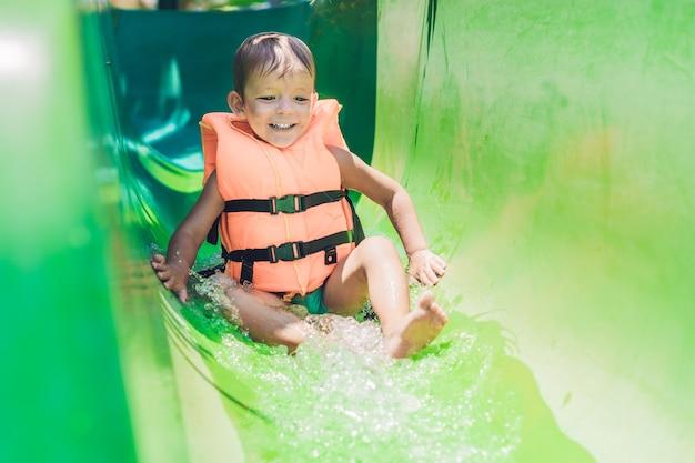 Ein junge in einer schwimmweste rutscht von einer rutsche in einem wasserpark herunter.