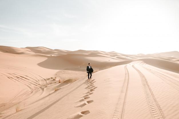 Ein junge in seinem hochzeitsanzug, der auf den dünen der wüste mit dem sonnenaufgang im hintergrund geht