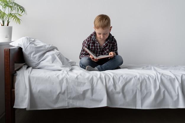 Ein junge in selbstisolation liest ein buch und bleibt zu hause