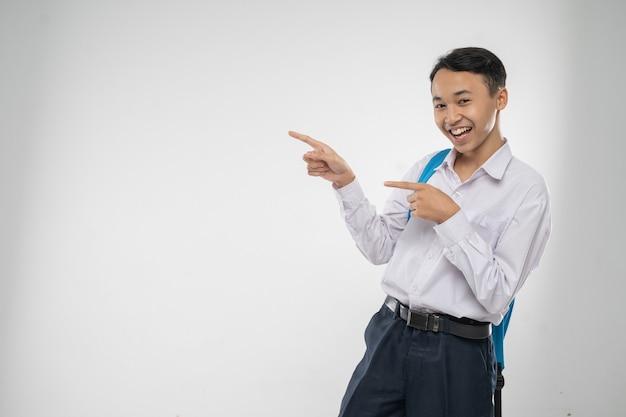 Ein junge in uniform der junior high school, der mit dem finger darauf lächelt, wenn er einen rucksack mit kopien trägt...