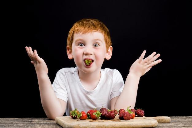 Ein junge isst reife erdbeeren