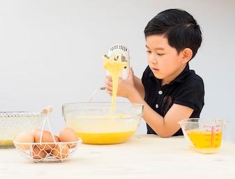Ein Junge macht Kuchen. Foto ist auf sein Gesicht gerichtet.