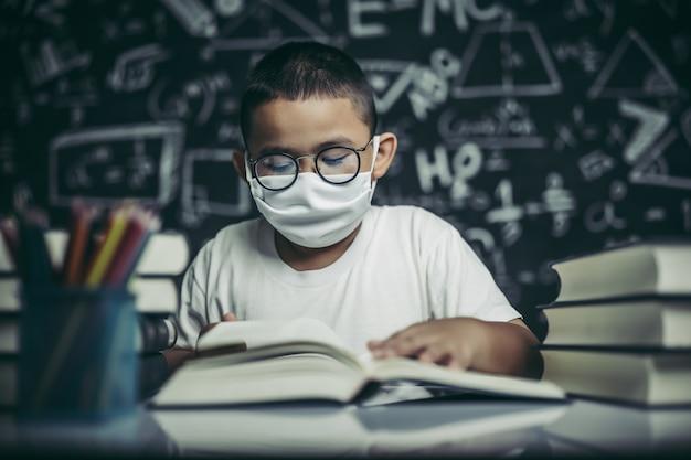 Ein junge mit brille sitzt im klassenzimmer und liest