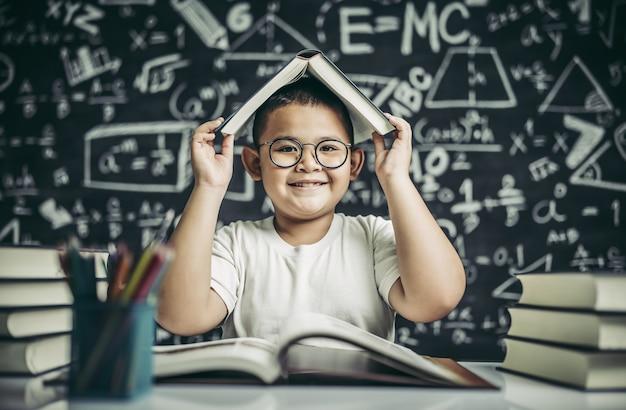 Ein junge mit brille studierte und legte im klassenzimmer ein buch auf den kopf.