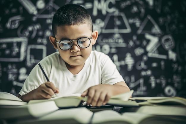 Ein junge mit brillenmann, der im klassenzimmer schreibt
