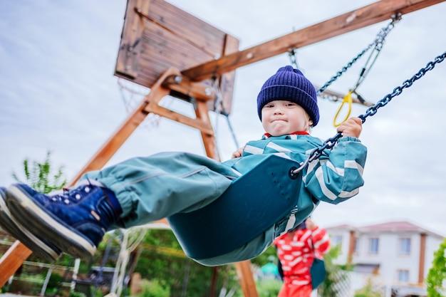 Ein junge mit down-syndrom spielt auf dem spielplatz, er schwingt auf einer schaukel. genetische erkrankung bei einem kind. selektiver fokus