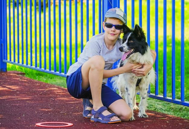 Ein junge mit dunkler brille sitzt und umarmt einen hund.