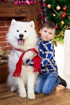 Ein junge mit einem großen hund zu weihnachten.