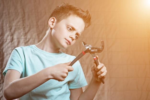 Ein junge mit einem schraubenschlüssel und überraschten augen repariert