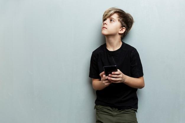 Ein junge mit einem telefon in der hand steht und schaut auf. grauer hintergrund. platz für text.