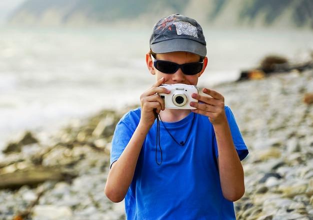 Ein junge mit einer kamera schießt im sommer auf das meer.