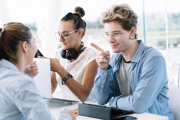 Ein junge mit erhobenem finger und einem mit einem rechten gesichtsausdruck geschlossenen auge sitzt an einem tisch