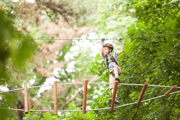 Ein junge mit helm und sicherheitsausrüstung im abenteuerseilpark vor dem hintergrund der natur