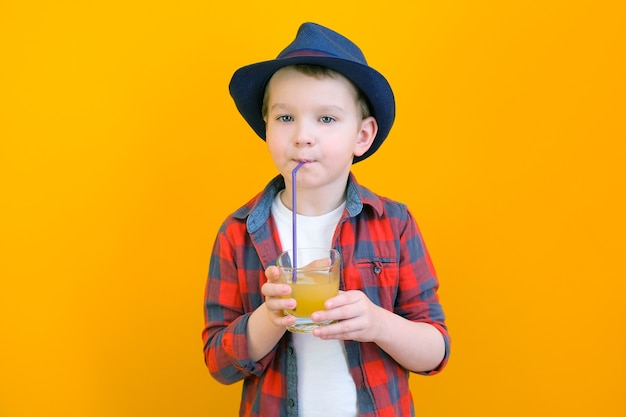 Ein junge mit hut trinkt saft mit einem strohhalm. entspannendes konzept. gelber hintergrund platz für ihren text. attrappe, lehrmodell, simulation