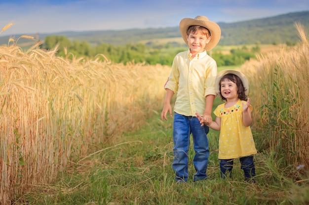 Ein junge mit kleinem mädchen nahe einem gelben weizenfeld