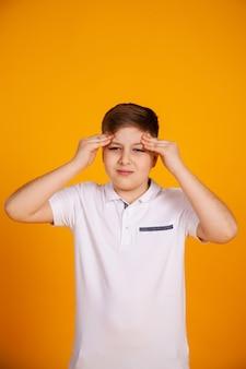 Ein junge mit kopfschmerzen. kaukasisches kind auf einem gelben hintergrund, der unter kopfschmerzen und migräne leidet.
