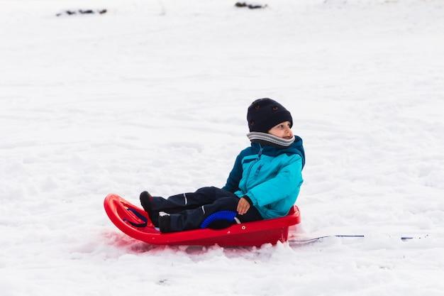 Ein junge mit rotem schlitten im schnee