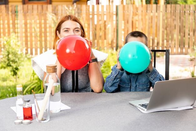 Ein junge mit seiner mutter bläst an einem warmen sommertag im garten zwei bunte luftballons auf. geburtstagsvorbereitung