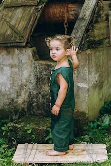 Ein junge mit weißen haaren in einer grünen kombination spielte an einem brunnen