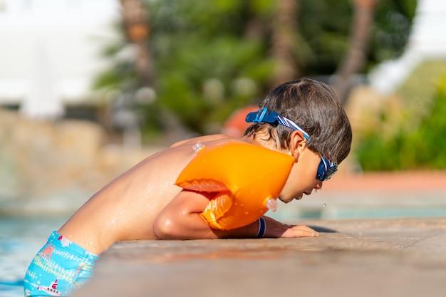 Ein junge nach dem schwimmen im pool. kleines kind in brille und armstulpen.