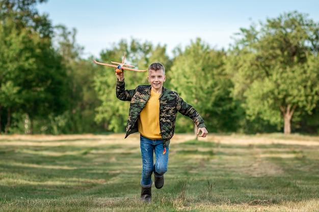 Ein junge rennt über das feld und startet ein spielzeugflugzeug.