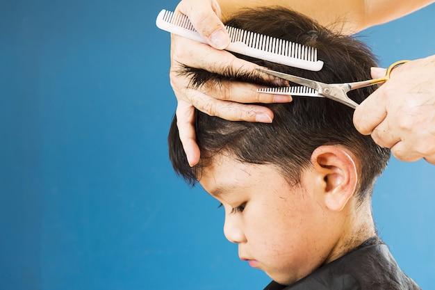 Ein junge schneidet sein haar von einem friseur ab