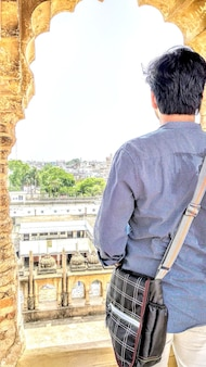 Ein junge sieht das dekorative geländer von bara imambara in lucknow, bundesstaat uttar pradesh, indien