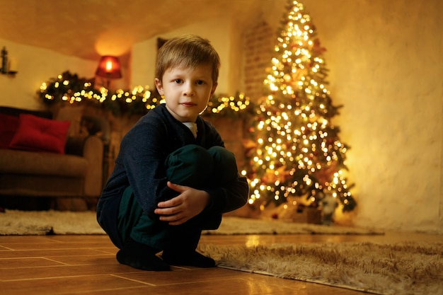 Ein junge sitzt am vorabend des neuen jahres in einem festlichen raum auf dem boden
