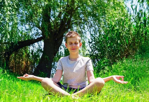 Ein junge sitzt auf einem grünen rasen in der lotus-position und meditiert.
