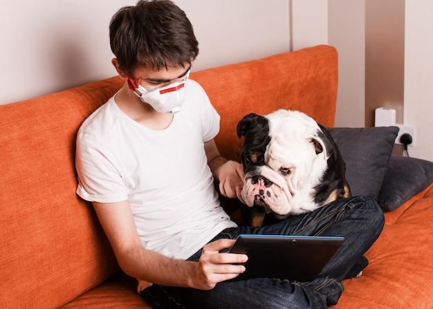 Ein junge sitzt auf einem sofa, trägt eine gesichtsmaske und lernt oder lernt online auf dem tablet mit seinem weißen und schwarzen hund
