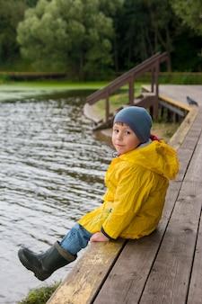 Ein junge sitzt in einem gelben regenmantel auf einer holzbrücke. ein kind auf einem spaziergang