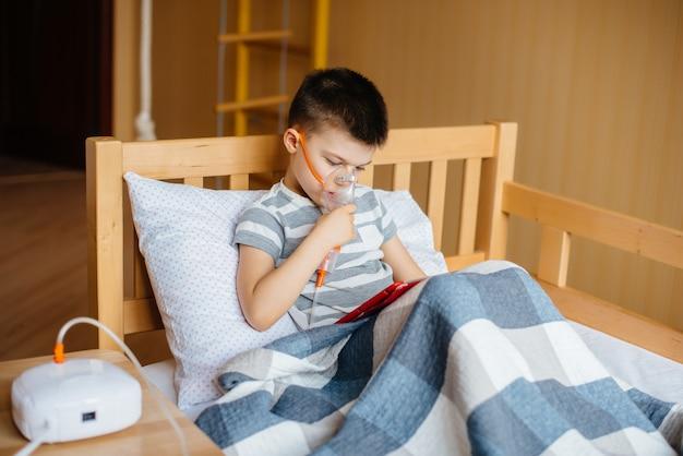 Ein junge spielt auf einer tablette während eines lungeninhalationsverfahrens. covid19, coronavirus, pandemie.