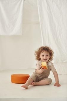 Ein junge steht in einem weißen raum und hält ein stück käse in der hand.