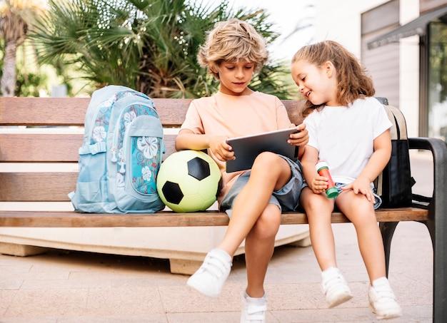 Ein junge und ein mädchen, die mit einem tablet spielen, gehen mit ihren rucksäcken zur schule