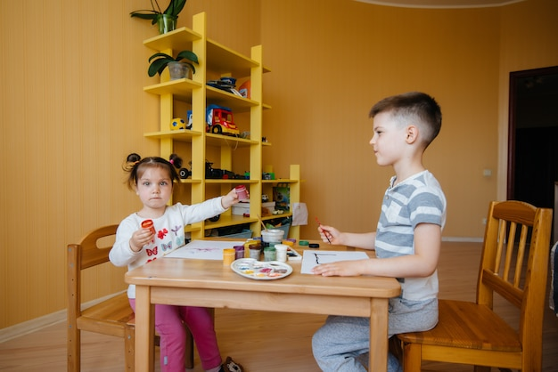 Ein junge und ein mädchen spielen zusammen und malen. erholung und unterhaltung. bleib zuhause.