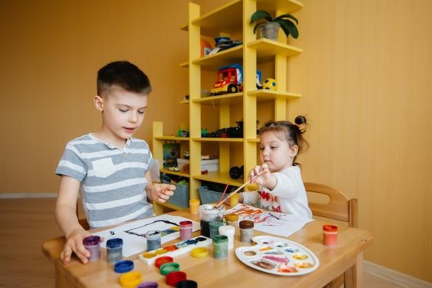Ein junge und ein mädchen spielen zusammen und malen