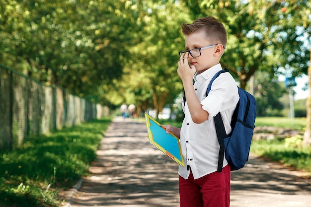 Ein junge von einer grundschule mit einem rucksack auf der straße