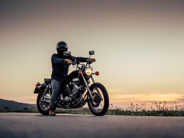 Ein junge wartet mit dem motorrad auf der straße